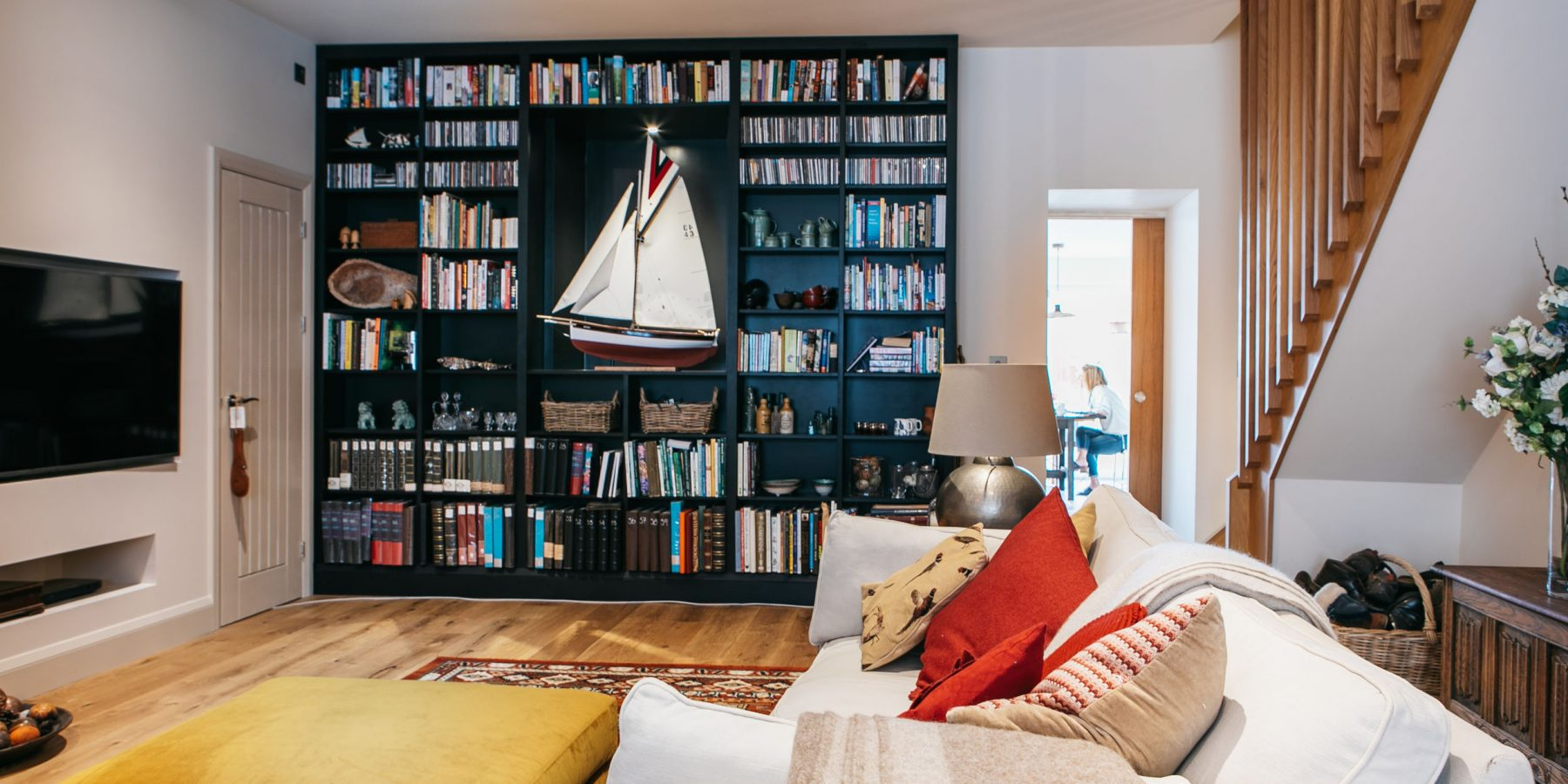 Dark bookcase displaying a model boat in a sitting room
