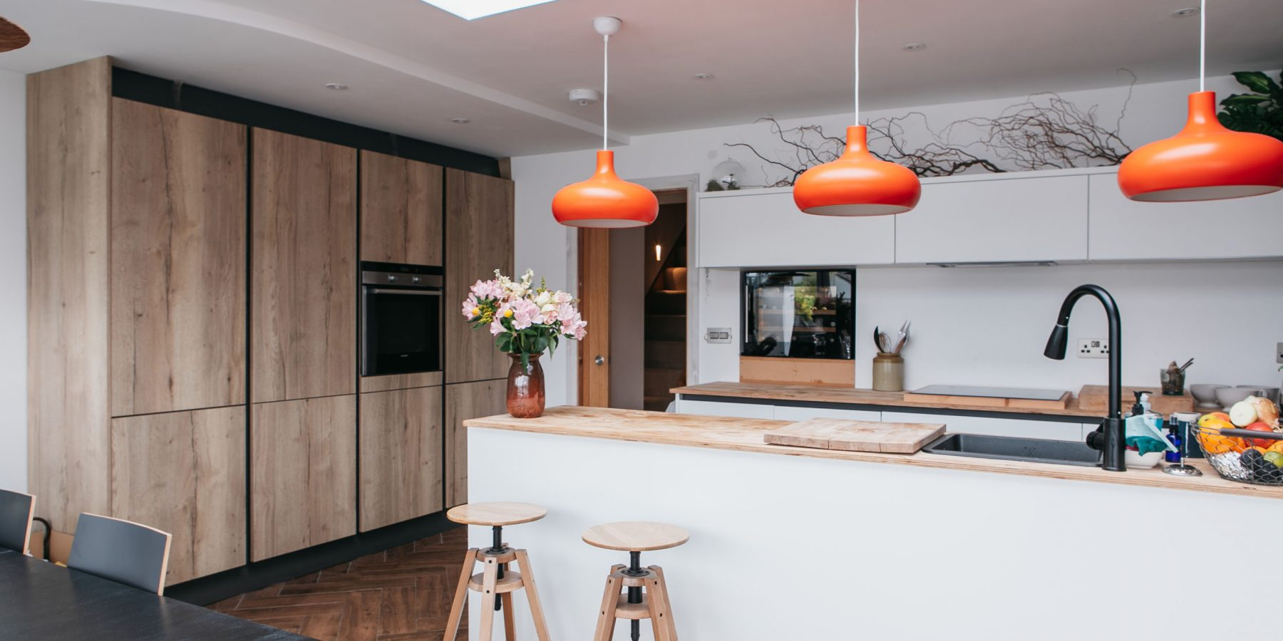 Thumbnail of http://White%20kitchen%20with%20orange%20lamps%20and%20wooden%20floor