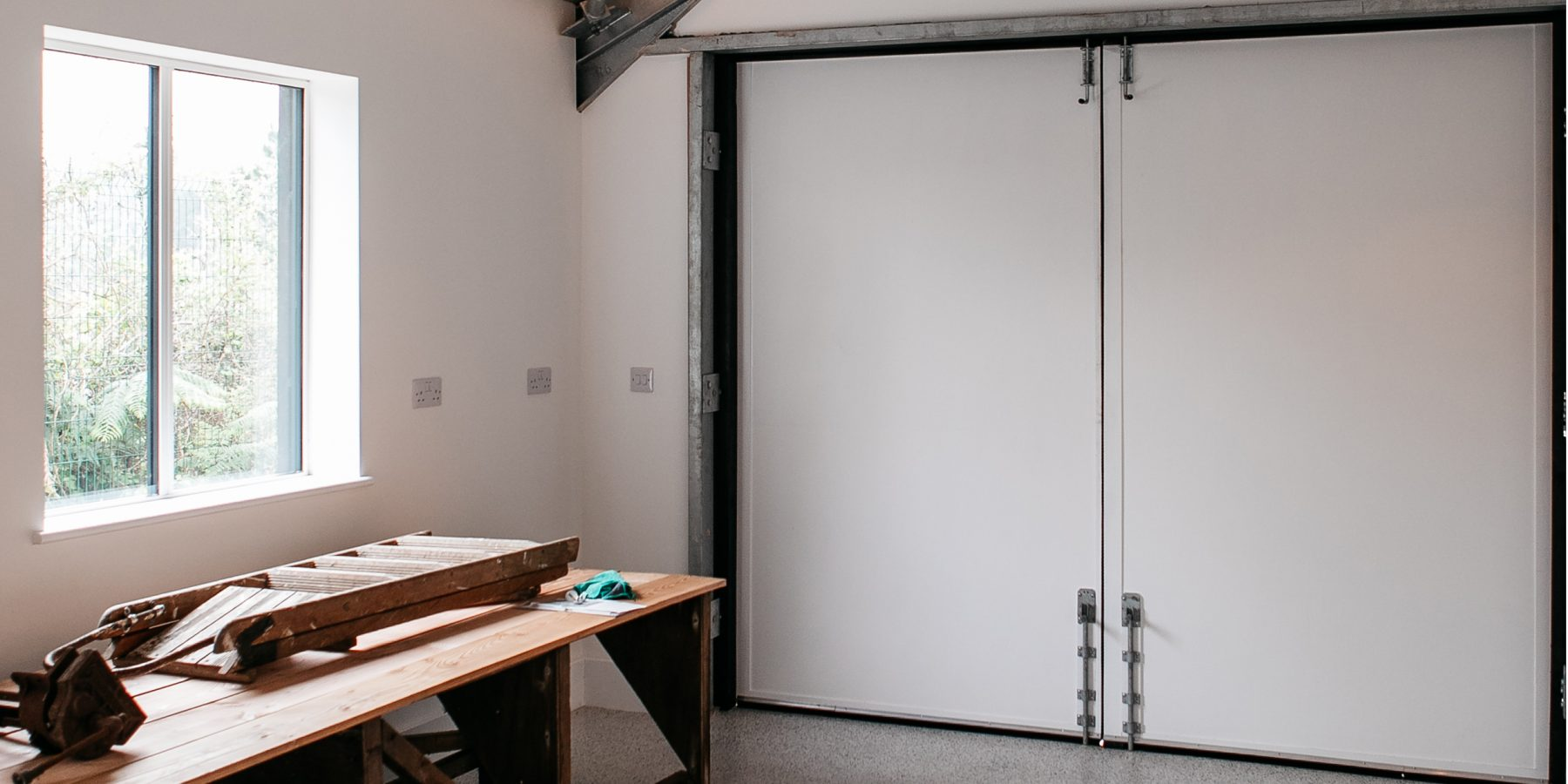 Thumbnail of http://Large%20warehouse%20style%20double%20doors%20next%20to%20a%20workbench