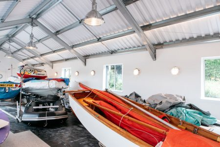http://Boathouse%20with%20high%20ceiling%20joined%20window%20with%20red%20boat%20inside