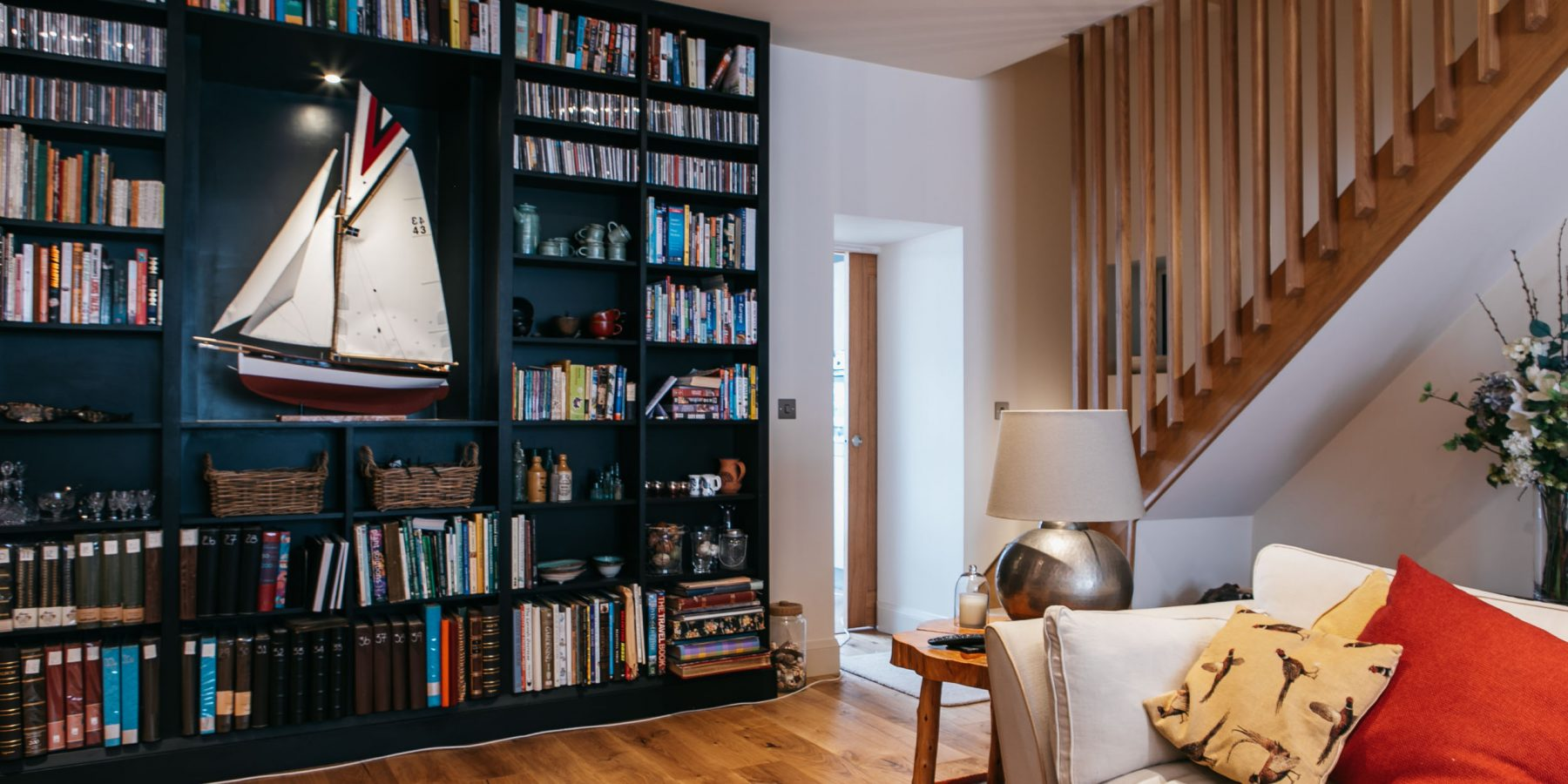 Dark custom joined bookcase displaying a model boat in a sitting room