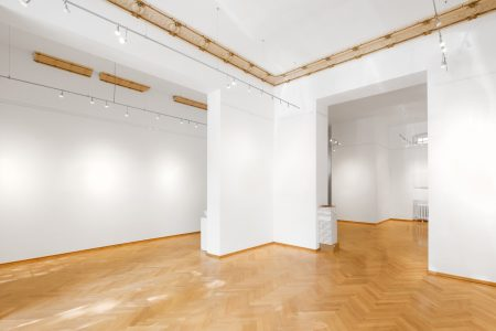 http://Empty%20art%20gallery%20with%20white%20walls%20and%20herringbone%20wood%20floor